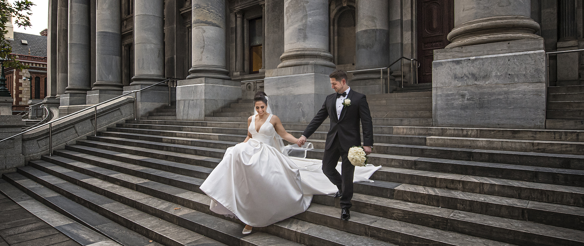 Bride and groom casually walking down the steps of parliment house in adelaide on their wedding day